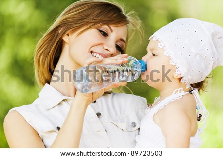 young charming caring mother gives daughter drink water bottles background summer green park - stock photo