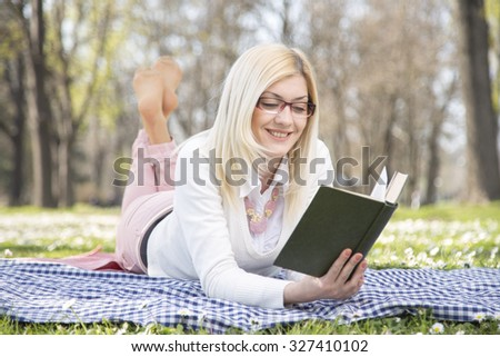 Young charming female concentrated is reading book while sitting in the fresh air in beautiful green park, attractive female is learning outdoors on the campus before start lectures in university