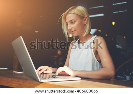 Young charming female freelancer using laptop computer for distance job while sitting in modern coffee shop interior, beautiful Caucasian woman working on net-book during morning breakfast in cafe bar - stock photo