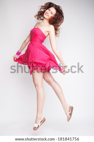 Young charming female in pink chiffon dress jumping over grey background  - stock photo