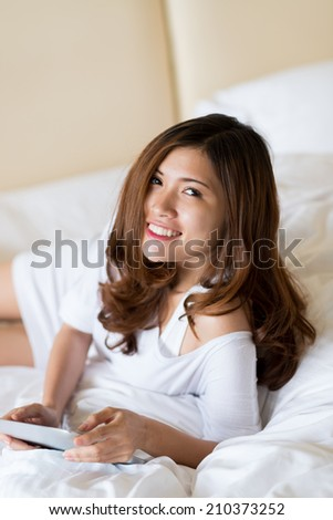 Young charming girl lying on duvet in the bedroom and using a digital tablet - stock photo