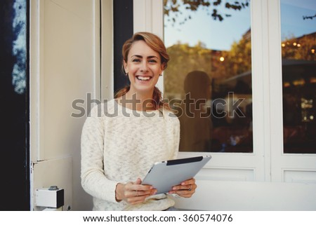 Young charming hipster girl with smiling face holding touch pad while sitting in coffee shop outdoors, happy joyful woman laughing at a funny video which she looked at digital tablet during free time - stock photo
