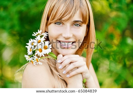 Young charming woman has control over bouquet of camomiles and smiles, against green summer nature. - stock photo