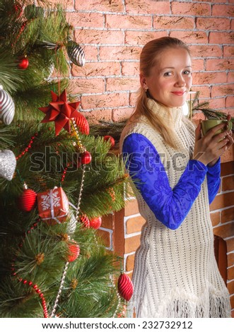 Young charming woman in white dress standing nearby Christmas tree with mug of hot drink - stock photo