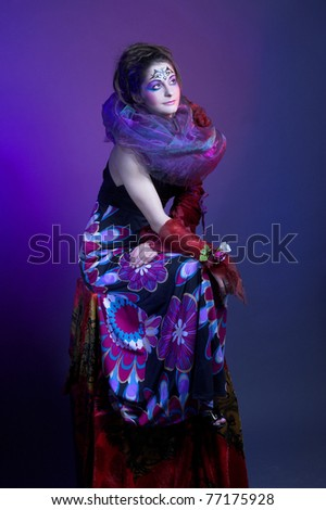 Young charming woman with bright make-up and in silk scarf.