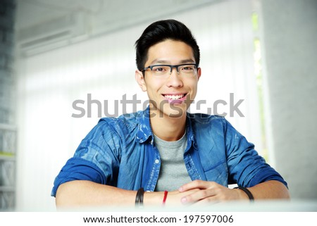 Young cheerful asian man sitting at the table - stock photo