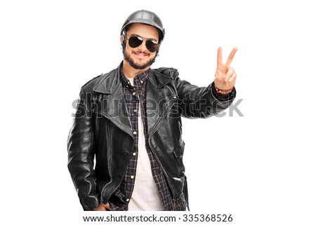 Young cheerful biker in a black leather jacket making a peace hand gesture isolated on white background - stock photo