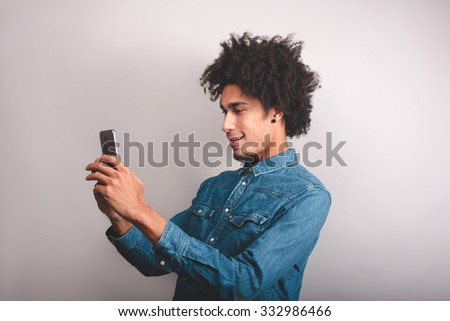 Young cheerful black man typing something on the mobile phone. - stock photo