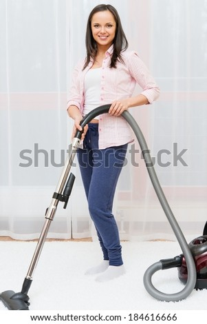 Young cheerful brunette woman vacuum cleaning carpet in home interior  - stock photo