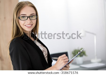 Young cheerful business woman standing with clipping board in the office ready to write something. - stock photo