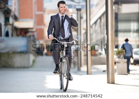Young cheerful businessman riding a bicycle and using phone go to work  - stock photo