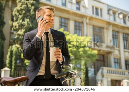 Young cheerful businessman riding a bicycle and using phone go to work. - stock photo