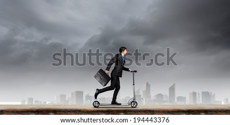 Young cheerful businessman riding scooter against city background