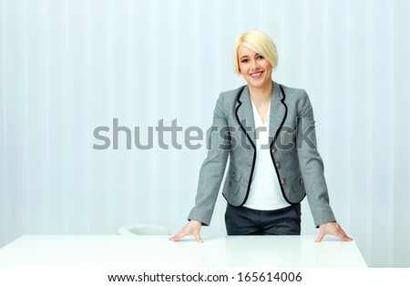 Young cheerful businesswoman in casual cloth standing at her workplace in office - stock photo