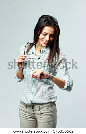 Young cheerful businesswoman looking at her watch on wrist on gray background - stock photo