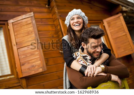 Young cheerful couple in a cabin in romantic scape in winter - stock photo