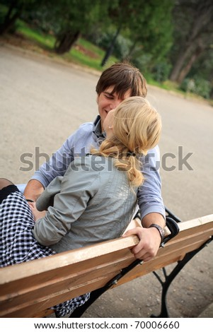 Young cheerful couple in the park- side view