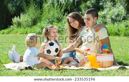 Young cheerful family of four on picnic in park at summer day. Focus on girl