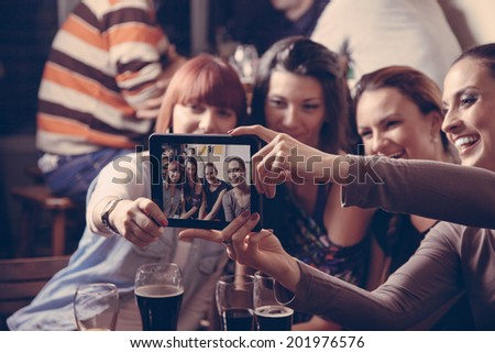 Young Cheerful Female Friends Taking Selfie In Pub Using Digital Tablet - stock photo