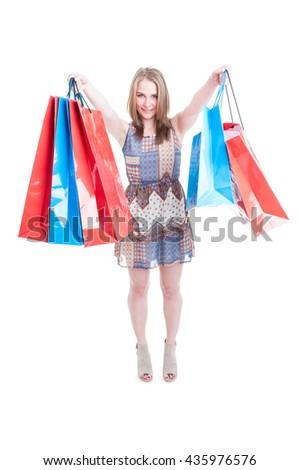 Young cheerful female rising up many shopping bags enjoying sales isolated on white background - stock photo