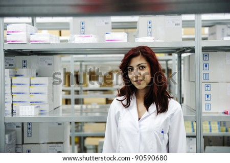 Young cheerful female worker in modern warehouse - stock photo