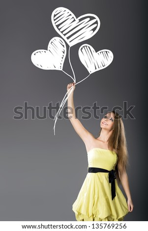Young cheerful girl hold hand-drawn white hearts balloons - stock photo
