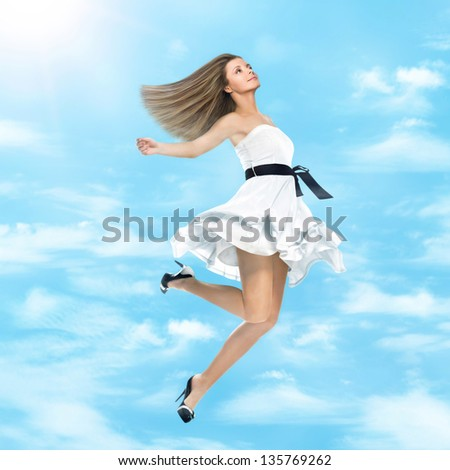 Young cheerful girl in white dress flying in the sky - stock photo