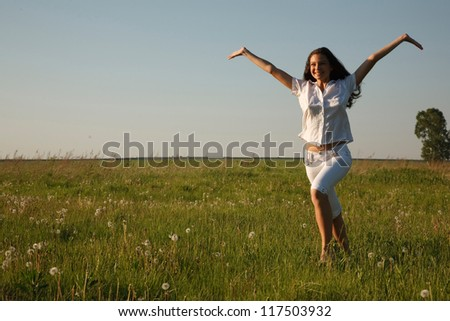 Young cheerful  girl is running on the field with her arms outstretched