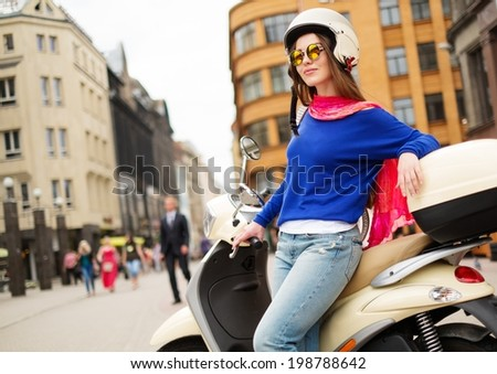 Young cheerful girl near scooter in in european city  - stock photo