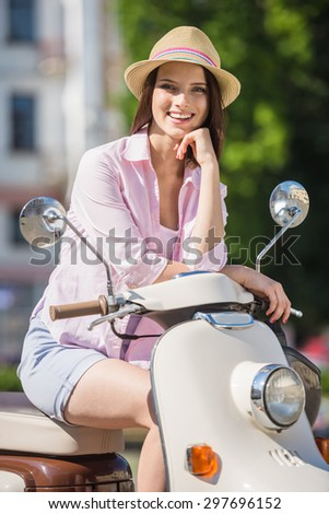 Young cheerful girl sitting on scooter in european city. - stock photo