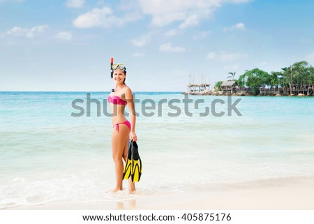 Young, cheerful, gorgeous lady being happy with diving mask and flippers on secret beach in Thailand.