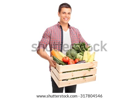 Young cheerful man carrying a wooden crate full of fresh vegetables isolated on white background - stock photo