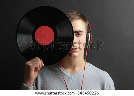 Young cheerful man listening to music on headphones and holds the vinyl in hand, on a black background.