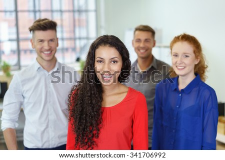 Young Cheerful Office Woman Smiling at the Camera Against Three Colleagues. - stock photo
