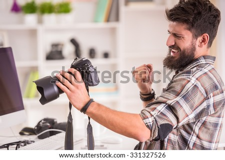 Young cheerful photographer with beard, while working in his office