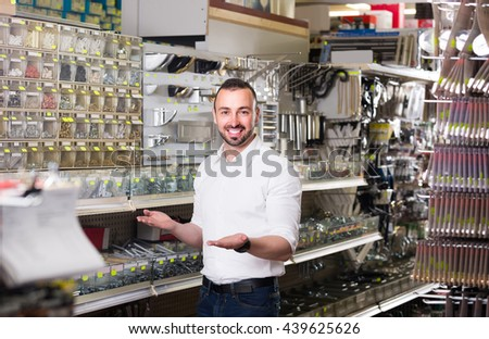 Young cheerful russian man standing next to showcase with various plastic rawlplugs and  choosing one