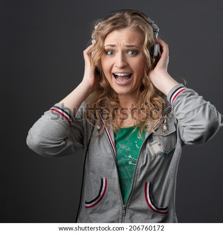 young cheerful screaming casual caucasian woman with headphones over gray background - stock photo