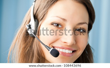 Young cheerful smiling support phone female operator in headset at office - stock photo