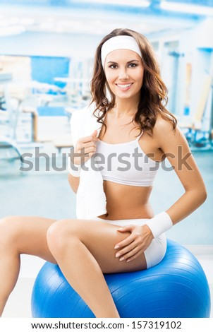 Young cheerful smiling woman exercising with fitball at fitness club or gym - stock photo