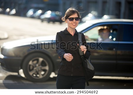 Young cheerful smiling woman with backpack crossing the road at pedestrian crosswalk, walking in sunny European city street in summer, blurred riding car on the background - stock photo