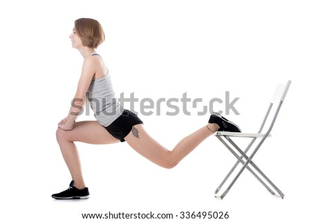 Young cheerful sporty attractive woman doing fitness training, exercises for hips and buttocks with office chair, full length isolated studio image on white background - stock photo
