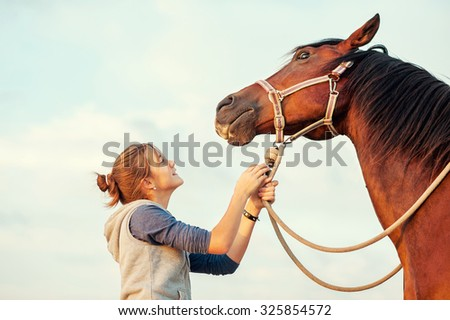 Young cheerful teenage girl calming big spirit chestnut horse. Vibrant multicolored summertime outdoors horizontal image with filter. - stock photo