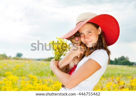 Young cheerful teenage girl hugging her little dog in field with bouquet of yellow flowers. Multicolored summertime outdoors horizontal image. - stock photo