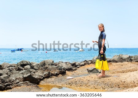 Young cheerful teenage girl in diving suit with paddles standing on Atlantic ocean rock coast. Tenerife, Canary islands, Spain. Vibrant multicolored summertime horizontal outdoors image.