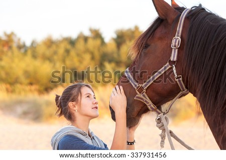 Young cheerful teenage girl stroking her big lovely horse's nose. Vibrant multicolored summertime outdoors horizontal image. - stock photo