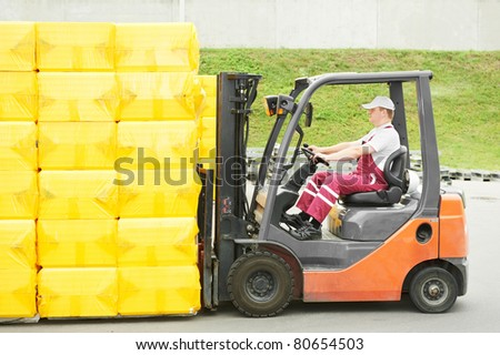 young cheerful warehouse worker driver in uniform driving forklift stacker loader - stock photo