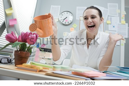 Young cheerful woman at work watering pink flowers on her desk. - stock photo