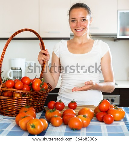Young cheerful woman cooking tomatoes in the kitchen - stock photo