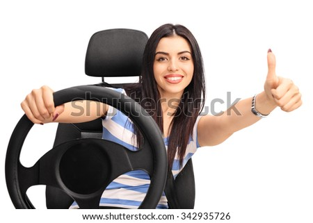Young cheerful woman driving a vehicle and giving a thumb up isolated on white background - stock photo