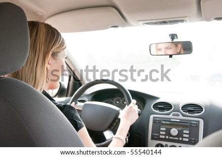 Young cheerful woman driving car - rear view, reflexion of eyes in mirror - stock photo